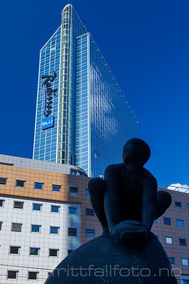 Skulptur under høye bygninger i Oslo.
