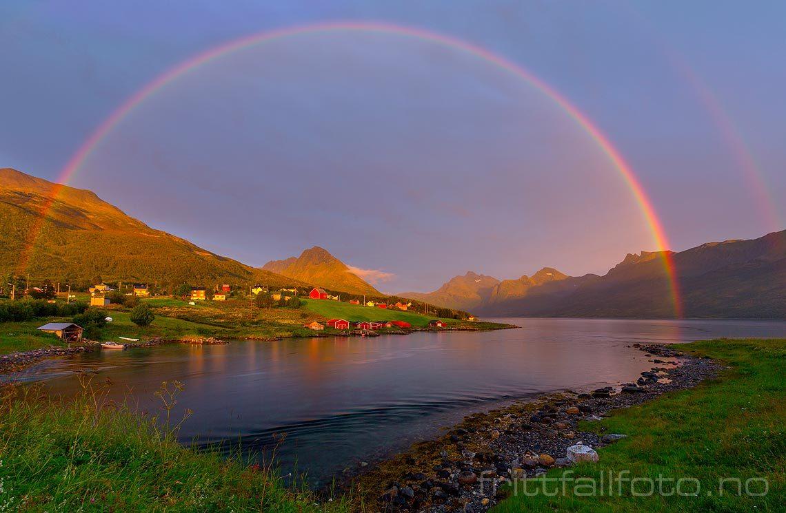 En regnbue i kveldssola rammer inn Åndervåg på Andørja, Ibestad, Troms og Finnmark.<br>Bildenr 20160808-542.