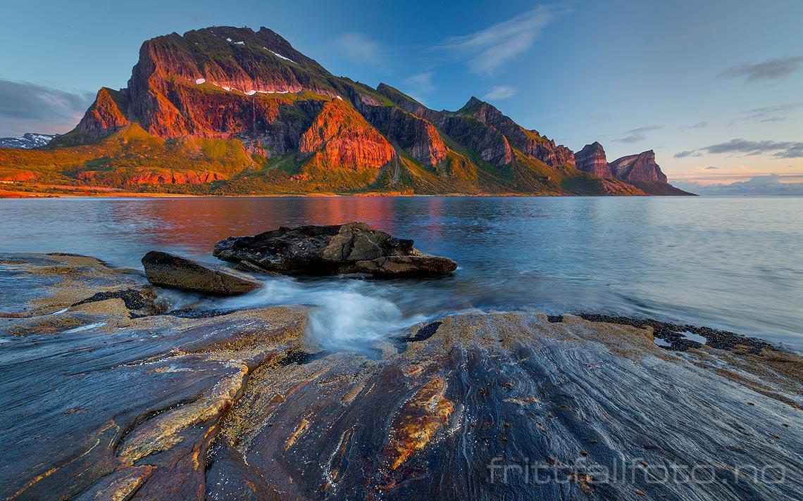 Sommerdagens siste solstråler sveiper over fjellrekka ved Fugløyfjorden i Gildeskål, Nordland.