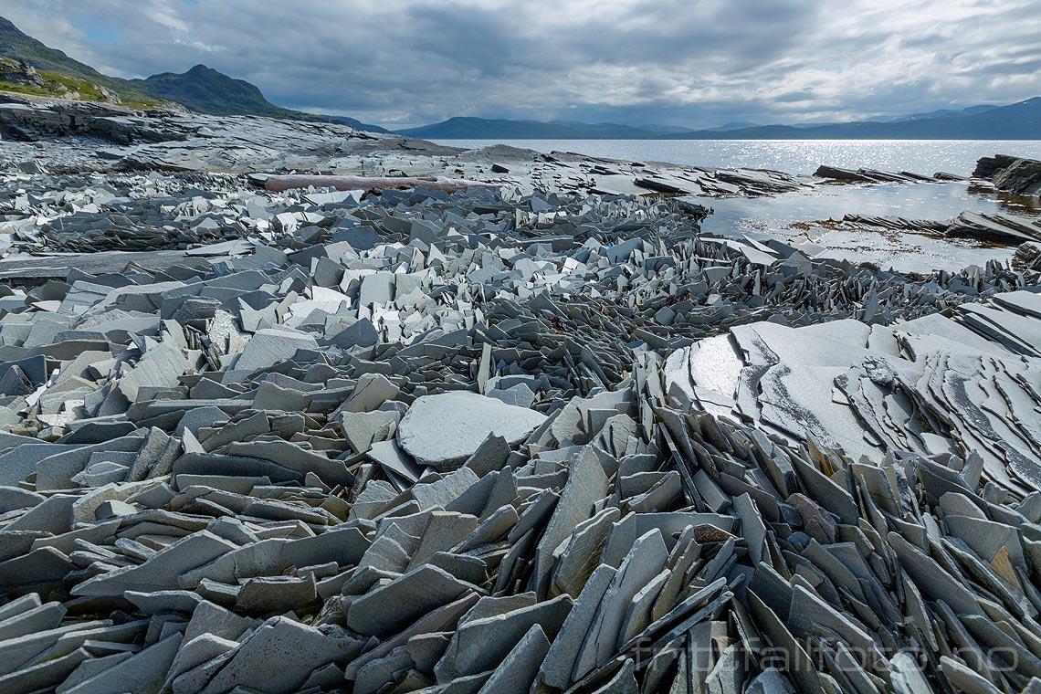 Et helt spesielt naturfenomen har oppstått her ved Revsbotn i Måsøy, Troms og Finnmark. Flak av skifer er vasket opp på svabergene omtrent som isflak om vinteren.<br>Bildenr 20170802-187.
