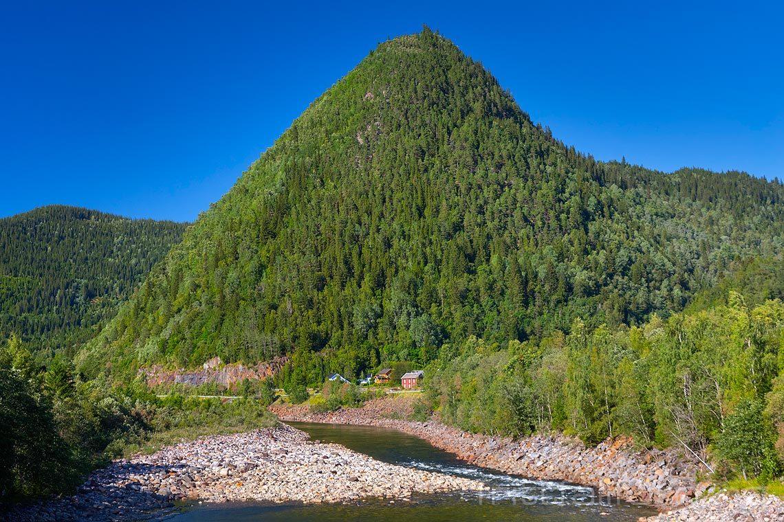 Rødstenen står som en sukkertopp ved Gaula nær Rognes i Gauldalen, Midtre Gauldal, Trøndelag.<br>Bildenr 20150818-339.
