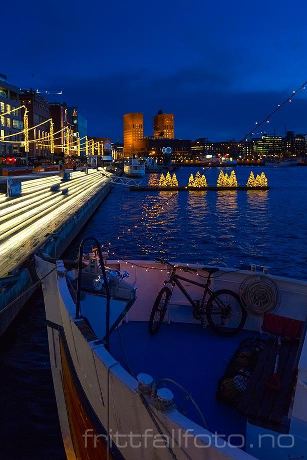 Vinterbelysning på Aker Brygge, Oslo. Oslo rådhus i bakgrunnen.<br>Bildenr 20151211-110.