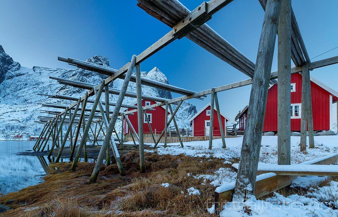 Røde rorbuer bak fiskehjeller ved Reine på Moskenesøya, Moskenes i Lofoten, Nordland.<br>Bildenr 20181208-247.