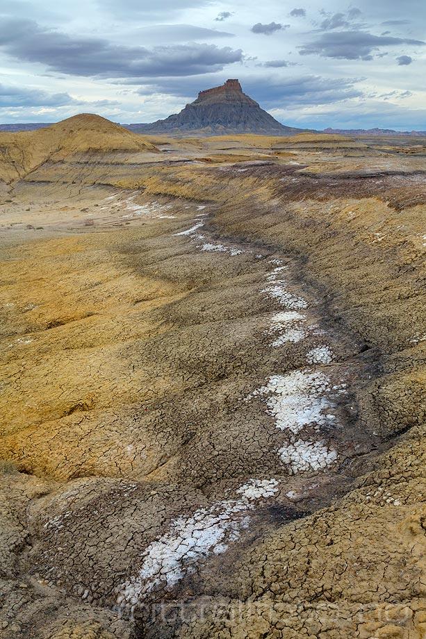Factory Butte vokter et øde landskap ved Upper Blue Hills, Wayne County, Utah, USA.<br>Bildenr 20170407-521.